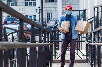 man with carryout food bags wearing a mask