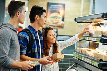 three students in food line