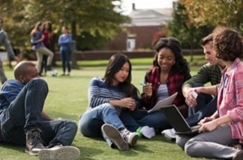 students sitting outside on lawn